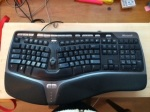I rest this ergonomic split keyboard on my lap, with my feet elevated on a step stool, for best working posture.
