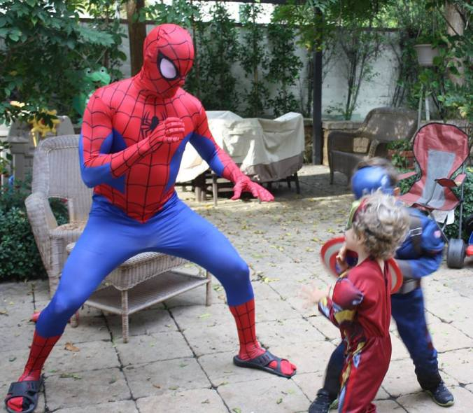 J as an adult dressed in a Spiderman costume fighting crime with his two young sidekicks Captain America and Ironman