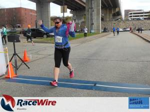Lisa crossing finish line of a 5K foot race